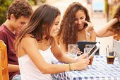 Teenage Friends Sitting At Caf�?�¢?? Using Digital Devices