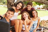 Group Of Teenagers Sitting On Bench Taking Selfie In Park
