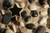 Close-up Of Stones And Star Sticking Out Of The Sand In The Sunlight