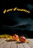picture of happy halloween  - Carved Halloween pumpkin smiling in the night next to leaves - JPG