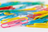 Bright multicolored office paperclips on white desktop closeup