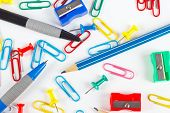 Pencil pen paperclips sharpeners and thumbtacks on white desktop