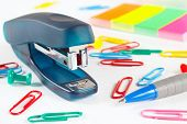 Stapler and multicolored stationery on white desktop closeup