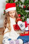 Little girl with long hair near Christmas tree