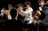 foto of directional  - Conductor directing symphony orchestra with performers on background - JPG