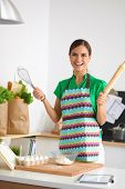 Smiling young woman in the kitchen, isolated on background