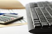 Keyboard of laptop, calculator, document lying on the desk