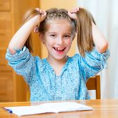 Funny little girl studying at home and smiling