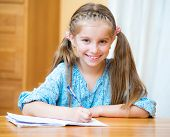 Cute little girl studying at home and smiling