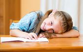 Small girl lying on a desk in a classroom