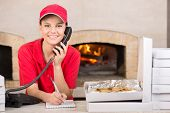 stock photo of take out pizza  - Smiling delivery young woman of pizza on the phone. The boxes of pizza on the table. ** Note: Shallow depth of field - JPG