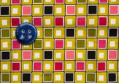 blue button on colourful fabric background