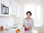 Happy Woman Preparing A Cup Of Coffee In Her Kitchen