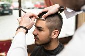 Hairdresser Shaving Man's Forehead With A Straight Razor