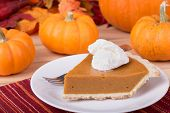 pic of pumpkin pie  - Slice of pumpkin pie with whipped topping and pumpkins in background - JPG