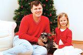 Family On Christmas Day Sitting Around The Christmas Tree