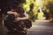 Boy and soldier in a military uniform say goodbye