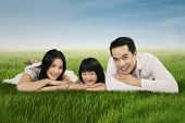 Joyful Asian Family Lying On Grass