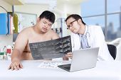 Physician Showing X-ray To Overweight Person