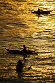 Silhouette Photo. Fishermen Catch Fish At Sunset. Beautiful Sunset Over A Tropical Sea.