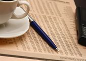 Cup of coffee near press and pen