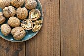 pic of walnut  - Walnut kernels and whole walnuts on plate on rustic old wooden background - JPG