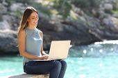 Woman Typing On A Laptop In A Tropical Beach