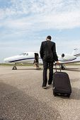 Full length rear view of businessman with luggage walking towards private jet