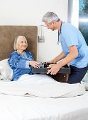 Male caretaker serving breakfast to senior woman on bed in nursing home