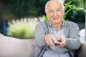 Portrait of elderly man using remote control while sitting on couch at nursing home porch
