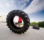 Female athlete flipping large tractor tire outdoors