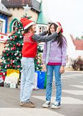 Side view of boy putting Santa hat on girl's head in courtyard