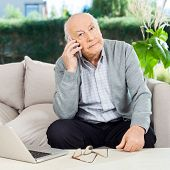 Portrait of senior man using smartphone while sitting on couch at nursing home porch