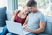 Loving couple surfing the web on a laptop computer as they sit arm in arm on the sofa at home