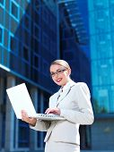 Pretty Young Businesswoman in White Posing with Laptop While Standing. Isolated on Blue Huge Buildin
