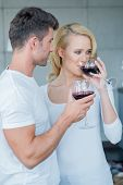 Young couple enjoying a glass of red wine as they stand arm in arm at a party or social event