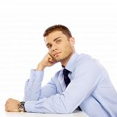 Sitting Young Salesman with Hand on Face Leaning on White Table. Looking at Camera. Captured in Stud