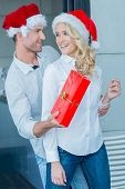 Playful man giving his wife a Christmas gift surprising her as he reaches round from behind in their