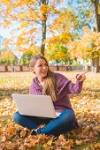 Happy Young Woman Sitting on Dried Leaves on the Ground with White Laptop. Looking at Left Frame.