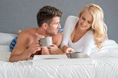 Sexy Sweet Middle Age Lovers on White Bed Having Drink on Cup. Captured on Gray Wall Background.