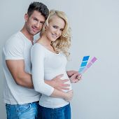 Young pregnant woman standing holding a pink and blue color card for a baby boy or girl as her husba