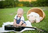 little boy with a guitar on the grass