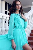 Beautiful Girl With Dark Hair In Luxurious Blue Dress Posing On Stairs