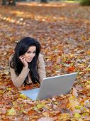 Pretty Smiling Young Woman Lying on Ground with Dry Leaves  with Apple Laptop. Looking at Camera Whi