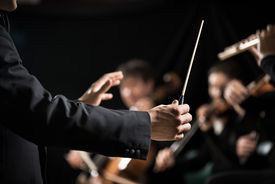 stock photo of conduction  - Conductor directing symphony orchestra with performers on background hands close - JPG