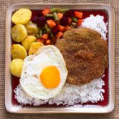stock photo of flat-bread  - Overhead shot of traditional Bolivian dish called Silpancho which is the name of the breaded flat round piece of beef meat served with fried egg rice fried potatoes and vegetables  - JPG