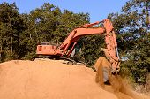 stock photo of track-hoe  - Large track hoe excavator working on large dirt pile on a new commercial development construction project - JPG