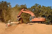 foto of track-hoe  - Large track hoe excavator loading a articulated dump truck with dirt from a new commercial development construction project - JPG