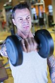 Man Making Dumbbell Front Raises - Workout Routine .
