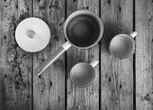 stock photo of saucepan  - Old cups and saucepan in a retro kitchen table setting in black and white - JPG